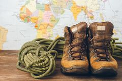 Brown shoes and sports rope on the background of the geographical map. Selective focus. Concept of travel and adventure. Horizontal frame stock photo
