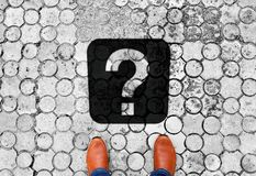 Brown shoes standing on the floor with question mark - meaning of life - next travel destination stock image