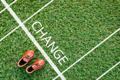 Brown shoes standing on the grass field with the word change.jpg Stock Photo