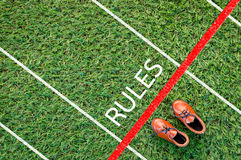 Brown shoes standing on the grass field with the word rules Royalty Free Stock Photography