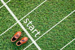 Brown shoes standing on the grass field with the word start Royalty Free Stock Photos