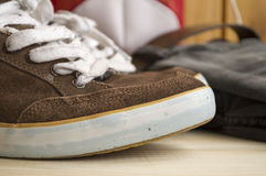 Brown shoes worn on the background of wood Royalty Free Stock Image