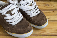 Brown shoes worn on the background of wood Stock Photos