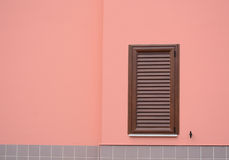 Brown shutter in a pink wall Stock Photos