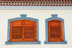 Brown shutters on a white wall stock images