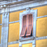 Brown shutters in a yellow wall Royalty Free Stock Photography