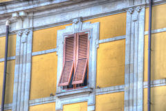 Brown shutters in a yellow wall Royalty Free Stock Photo