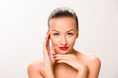 Brown sleek hair beautiful woman with hands close to face looking at the camara. Stock Photo