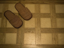 Brown Slippers on tile floor Royalty Free Stock Images