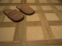 Brown Slippers on tile floor Stock Images