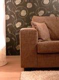 Brown-Sofa und Blumen-Wand-Papier lizenzfreies stockfoto