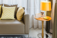 Brown sofa with yellow pillows and lamp Royalty Free Stock Photos