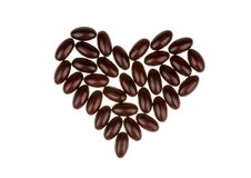 Brown softgel capsules in the shape of the heart isolated. Brown softgel capsules in the shape of the heart isolated on the white background Stock Image