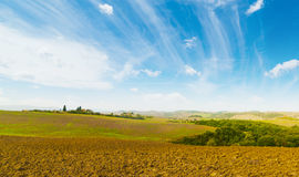 Brown soil under a blue sky in Tuscany. Italy Stock Image