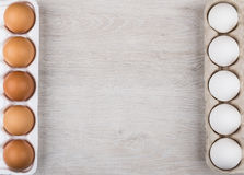 Brown and some white eggs on left and right. Rows of brown and some white eggs on left and right side of wooden table royalty free stock photo