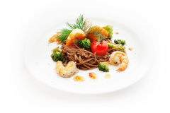 Brown spaghetti with shrimp, tomatoes, cauliflower Royalty Free Stock Image