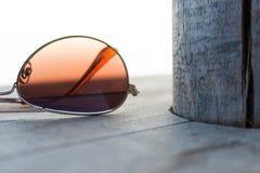 Brown spiegelte Sonnenbrille-Detail über den hölzernen Hintergrund-Abschluss oben und selektiven Fokus wider Lizenzfreie Stockfotos