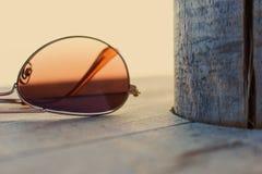 Brown spiegelte Sonnenbrille-Detail über den hölzernen Hintergrund-Abschluss oben wider Art und Weisekonzept Stockfotografie