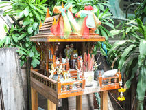 Brown spirit house in Thailand with flowers in a vase.  Stock Image