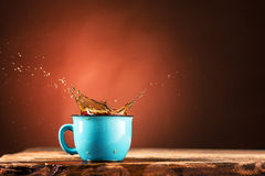 Brown splashes out drink from cup of tea on a brown background Stock Photography