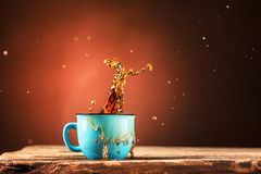 Brown splashes out drink from cup of tea on a brown background Royalty Free Stock Images