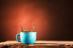 Brown splashes out drink from cup of tea on a brown background Royalty Free Stock Photography
