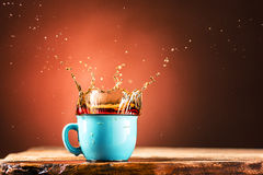 Brown splashes out drink from cup of tea on a brown background Royalty Free Stock Photo