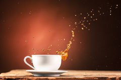 Brown splashes out drink from cup of tea on a brown background Stock Images