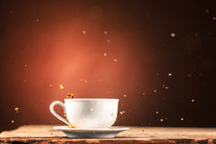 Brown splashes out drink from cup of tea on a brown background Stock Photo