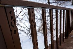 Brown staircase railing in winter against a background of tree branches stock photo