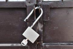 Brown steel door with padlock, unlocked. Stock Photos