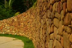 Brown-Steinwand mit kleiner Rasenfläche auf der Seite der Weise lizenzfreies stockbild