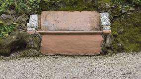 Brown stone bench. Ancient brown stone bench stuck in the rock Stock Images