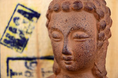 Brown stone Buddha statue with a woode background with stamps Royalty Free Stock Image