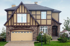 Brown stone cottage with beige garage and roof. New two-storied brown stone cottage with beige garage and roof Royalty Free Stock Images