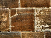 Brown stone wall. Square and rectangular stones in an old wall of a historical building Stock Photos
