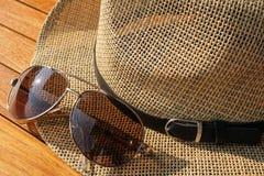 Brown Strawhat Beside Brown Aviator Sunglasses Stock Photo