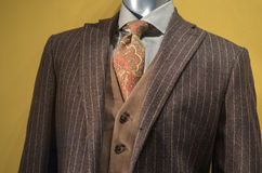 Brown striped suit. Close up of a mannequin in brown striped jacket, tan vest, checkered shirt and brown & orange tie royalty free stock photos