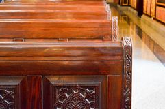 Strong beautiful wooden benches, seats in the church with carved patterns for prayers. stock image