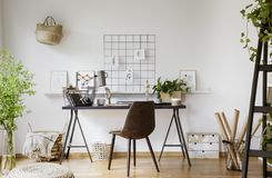 Brown-Stuhl am Schreibtisch mit Lampe im weißen Arbeitsplatzinnenraum mit p stockbild
