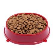 Brown suchy kot lub psi jedzenie w czerwonym pucharze odizolowywającym na białym backgrou Obrazy Royalty Free