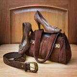 Brown suede bag, leather shoes and a belt. On wooden background Royalty Free Stock Photos