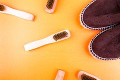 Brown suede espadrille shoes with brushes on yellow paper background. Stock Photos