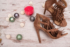 Brown suede shoes on a wooden background, Christmas decorations and candle. fashion concept Royalty Free Stock Image