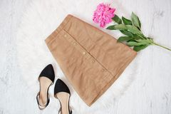 Brown suede skirt, black shoes and pink peony. Fashionable concept stock images
