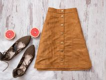 Brown suede skirt, brown suede shoes, cut grapefruit halves. Wooden background. Fashion concept Royalty Free Stock Images