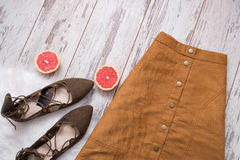 Brown suede skirt, brown suede shoes, cut grapefruit halves. Wooden background. Fashion concept. Top view stock photos