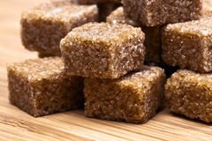 Brown sugar. Cubes on wooden board stock photo
