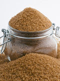 Brown sugar. Overflowing with brown sugar jar on white background stock photography