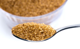 Brown sugar. Teaspoon of brown sugar, more sugar to the bottom stock photo